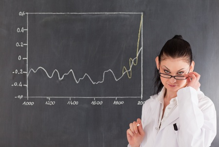 Dark-haired scientist standing near the blackboard and looking at the camera photo