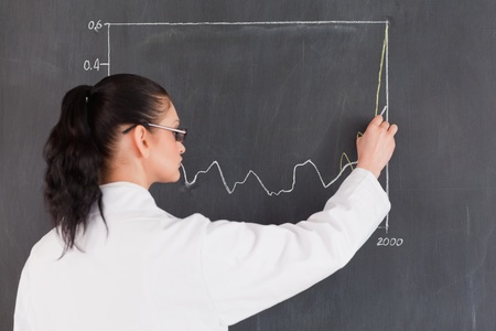 Dark-haired scientist drawing charts on the blackboard in a lab photo