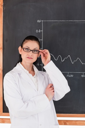 Female scientist standing near the blackboard and looking at the camera photo