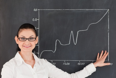 Scientist showing charts while standing near the blackboard in a lab photo