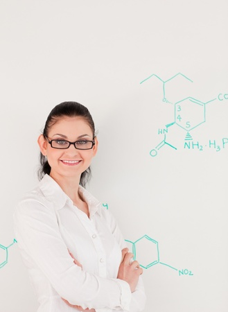 Dark-haired scientist woman looking at the camera while standing in front of a white board photo