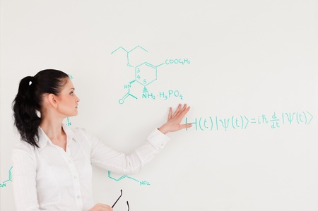 Scientist explaining a formula written on a white board to her students photo