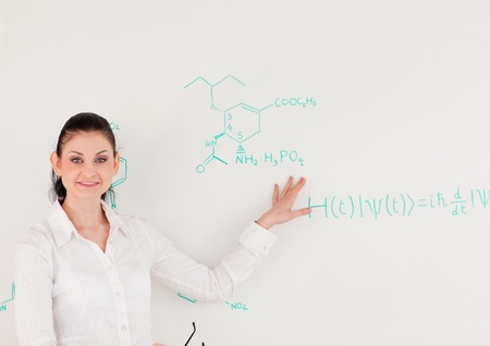 Female scientist looking at the camera while standing in front of a white board photo
