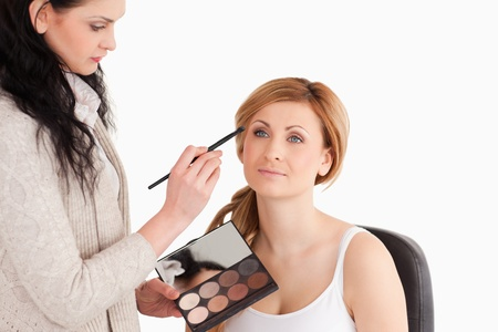 Cute blond-haired woman having her make up done by a make up artist in a studio photo