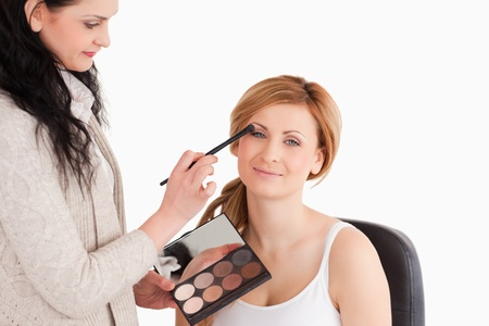 Attractive woman having her make up done by a make up artist in a studio photo