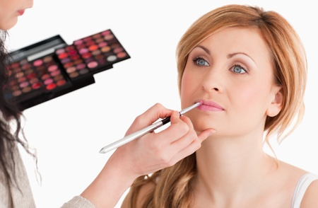 Cute woman having her make up done by a make up artist in a studio photo