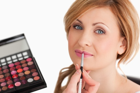 Young female having her make up done by a make up artist in a studio Stock Photo - 10205444