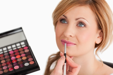 Cute female having her make up done by a make up artist in a studio photo