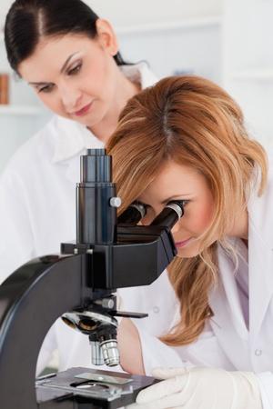 Netter Wissenschaftler Blick durch ein Mikroskop mit ihrer Assistentin in einem Labor