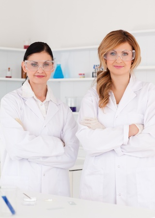 Two female scientists looking at the camera while standing in a lab photo