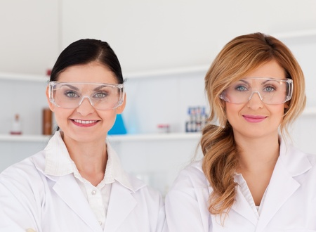 Two female scientists with safety glasses looking at the camera while standing in a lab photo