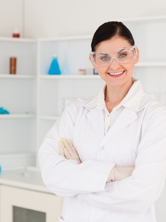 Dark-haired woman with safety glasses posing in a lab photo