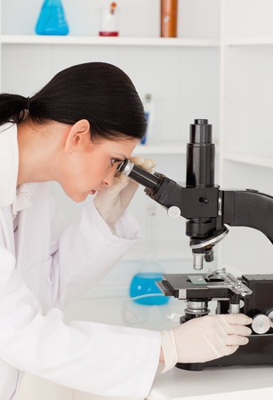 Dark-haired female looking through a microscope in a lab photo