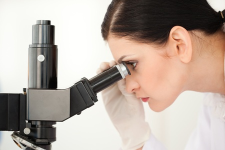 Scientist looking through a microscope in a lab photo