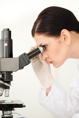 Female scientist looking through a microscope in a lab photo