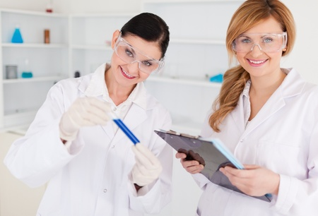 Two scientists looking at the camera while holding a test tube and a notapad in a lab Stock Photo - 10197488