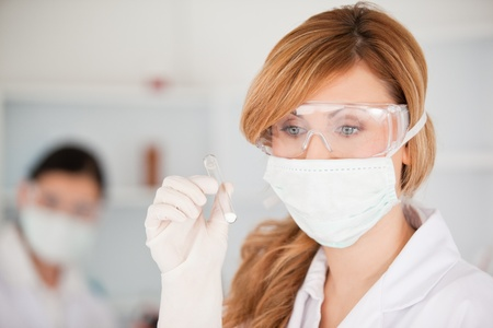 Blond-haired scientist wearing a mask and safety glasses and holding a  test tube in a lab photo