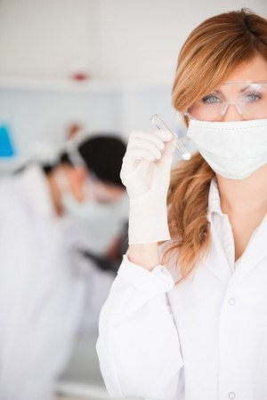 Cute scientist woman holding a test tube looking at the camera in a lab photo
