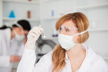 Blond-haired scientist observing a test tube in a lab photo
