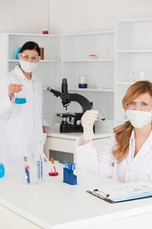 Scientists wearing safety glasses and masks in a lab photo