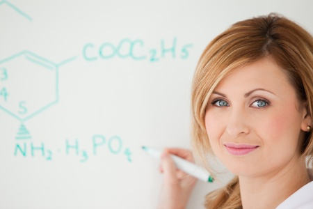 Blond-haired scientist looking at the camera while writing a formula on a white board in a lab photo