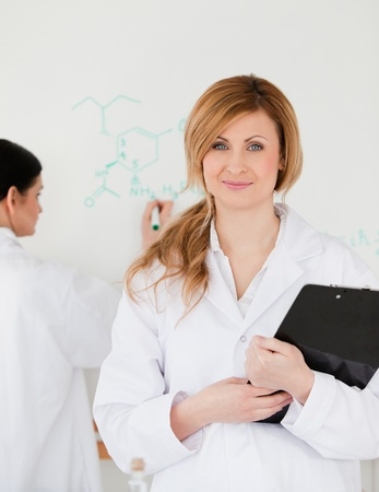 Two women in front of a white board in a lab photo