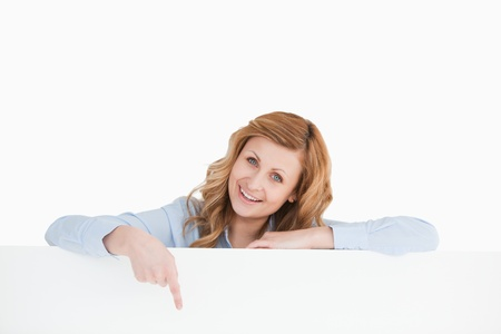 Cute blond-haired woman standing behind an empty white board while showing something Stock Photo - 10194180