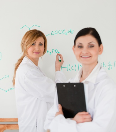 Young scientist writting a formula helped by her female assistant in a lab photo