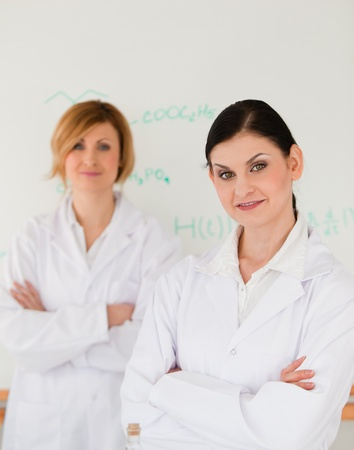 Two scientists posing in front of a white board in a lab photo
