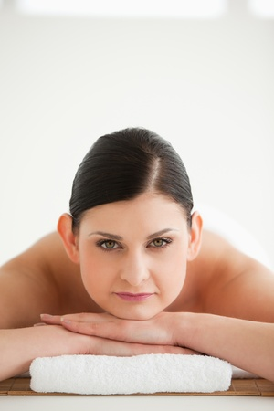 Dark-haired woman getting a spa treatment while looking at the camera photo