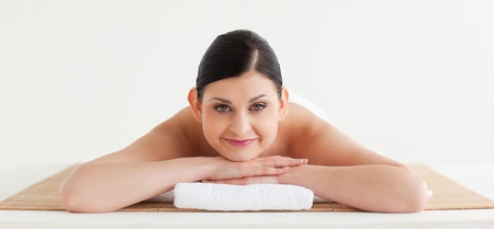 Brunette relaxing while looking at the camera in a spa centre photo