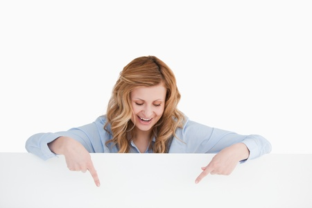 Smiling blond-haired woman standing behind an empty white board while showing something photo