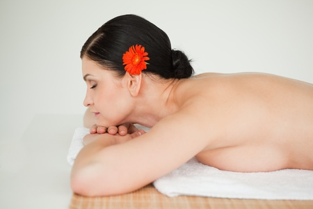Brunette relaxing lying down in a spa centre photo