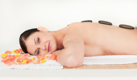 Lovely brunette enjoying the procedure of massage in a spa centre photo