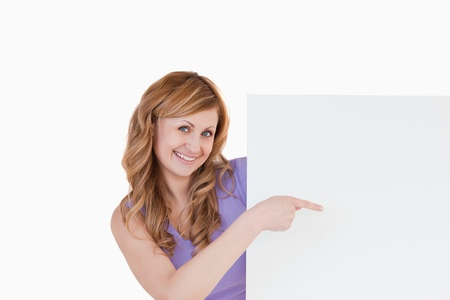Cute blond-haired woman holding a white board while showing something photo