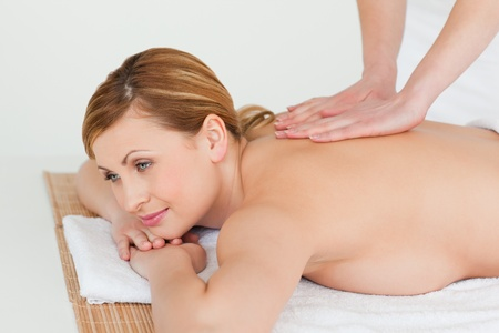 Young and attractive blond-haired woman getting a massage in a spa centre photo