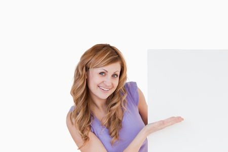 Happy blond-haired woman holding a white board while showing something photo