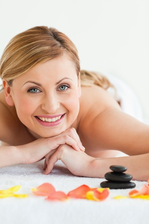 Pretty blond-haired woman looking at the camera while lying down in a spa centre photo
