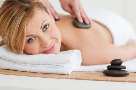 Therapist making a massage to a pretty blond-haired woman in a spa centre photo