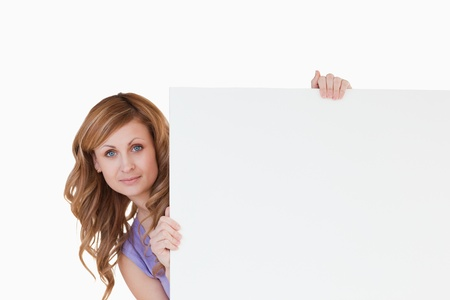 Cute blond-haired woman holding a white board photo