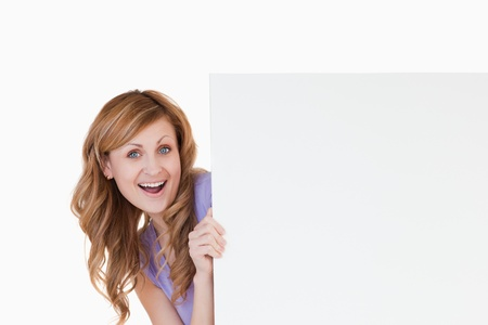Smiling blond-haired woman holding a white board photo