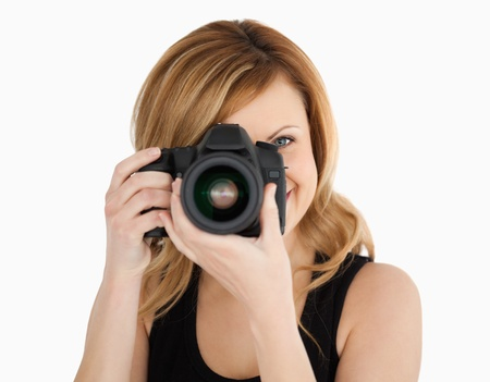 Blond-haired woman taking a photo with a camera on a white background photo