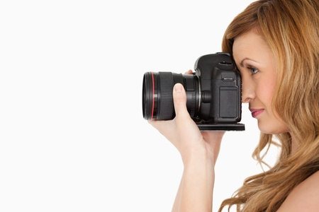 Pretty blond-haired woman taking a photo with a camera on a white background photo