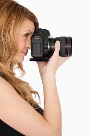 Sch�ne blonde Frau, die ein Foto mit einer Kamera auf einem wei�en Hintergrund Lizenzfreie Bilder