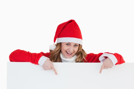 Attractive blond-haired woman dressed as Santa Claus holding a white board while showing something photo