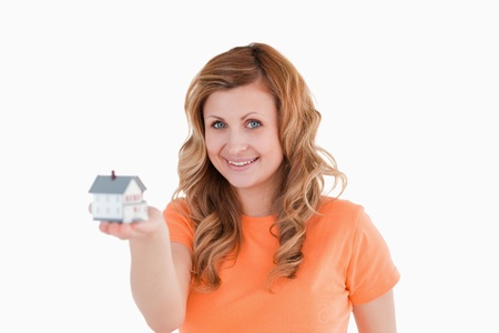 Attractive woman holding an house model on a white background photo