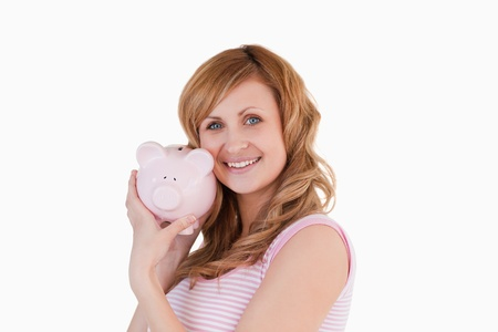 Cute woman posing with her piggybank on a white background photo