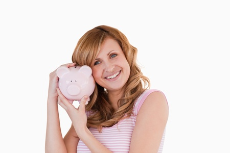 Cute woman smiling while holding her piggybank on a white background photo