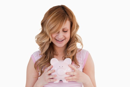 Lovely woman posing while holding her piggybank on a white background Stock Photo - 10195852