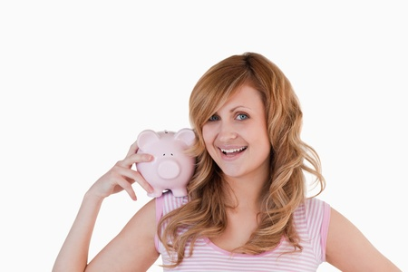 Blond-haired woman posing while holding her piggybank on a white background photo